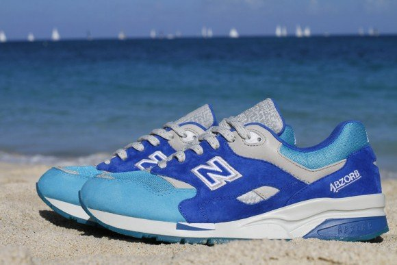 "The Nice Kicks x New Balance 1600 ""Grand Anse"" is combination of blues and grey on a white sole, representing the natural beauty of the scenery of Grand Anse."